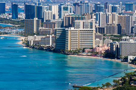 Photo pour Old beachfront hotels in Waikiki lining the coastline in the popular tourist attraction and resort in Honolulu, Oahu, Hawaii with a calm blue Pacific Ocean - image libre de droit
