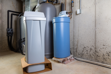 Photo pour Old and new water softener tanks in a utility room waiting for replacement to remove minerals from hard water - image libre de droit