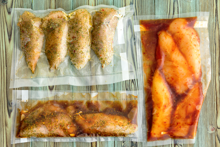 Photo pour Vacuum packed portions of lean chicken breast with assorted marinades and seasoned with spices and herbs ready for freezing or sous-vide cooking on rustic wood - image libre de droit