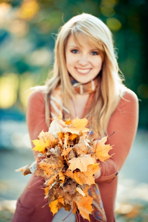 Blonde woman holding a bunch of autumn leaves