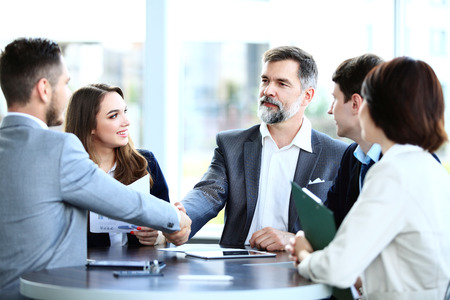 Photo pour Business people shaking hands, finishing up a meeting  - image libre de droit