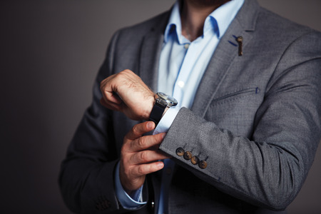 Photo pour Businessman checking time on his wristwatch  men s hand with a watch   - image libre de droit