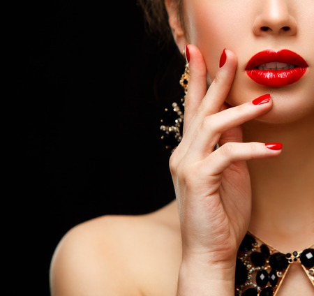 Foto de Red Sexy Lips and Nails closeup. Open Mouth. Manicure and Makeup. Make up concept. Half of Beauty model girl's face isolated on black background - Imagen libre de derechos
