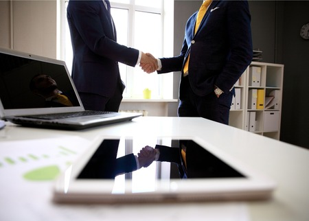 Photo pour Close-shot of a tablet computer with businessmen handshaking on background - image libre de droit