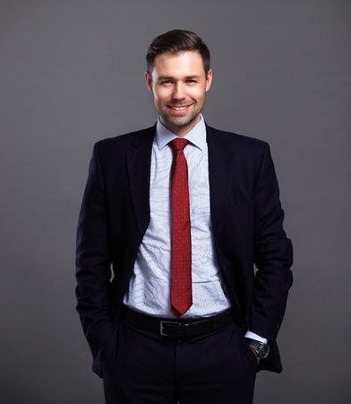 Foto de Cool businessman standing on grey background - Imagen libre de derechos