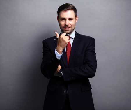 Photo for Cool businessman standing on grey background - Royalty Free Image