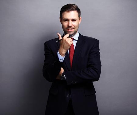 Photo pour Cool businessman standing on grey background - image libre de droit