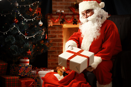 Photo pour Santa Claus brought gifts for Christmas and having a rest by the fireplace. Home decoration. - image libre de droit