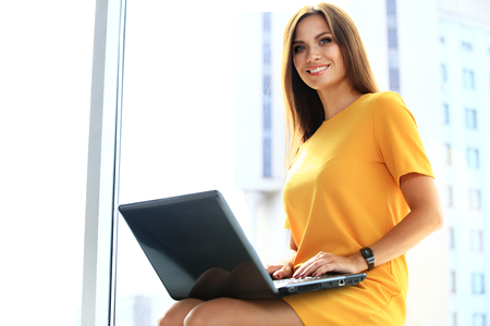 Photo for Portrait of a young business woman using laptop at office - Royalty Free Image