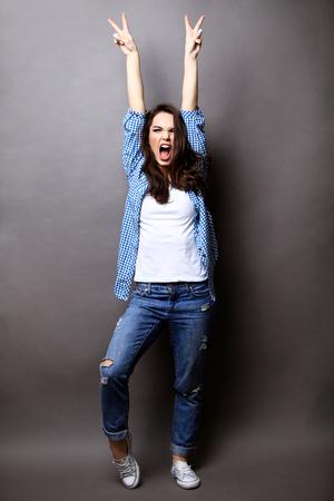 Photo pour Winner woman celebrating success Isolated on grey . - image libre de droit