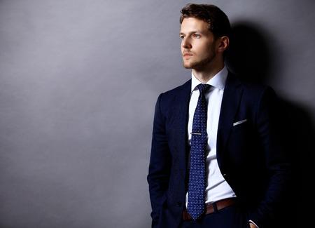 Photo pour Cool young businessman standing on grey background - image libre de droit
