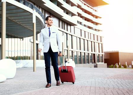 Foto de Businessman walking to hotel lobby. Full length portrait of young executive with a suitcase. - Imagen libre de derechos