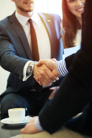Photo pour Business people shaking hands, finishing up a meeting. - image libre de droit