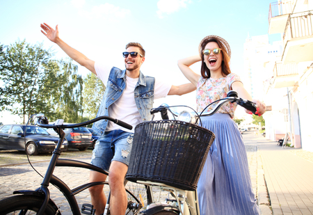 Photo pour Happy young couple going for a bike ride on a summer day in the city.They are having fun together. - image libre de droit