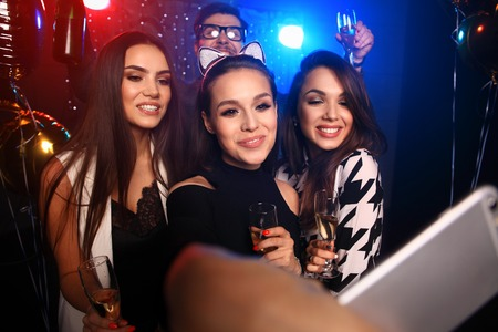 Photo pour party, technology, nightlife and people concept - smiling friends with smartphone taking selfie in club. - image libre de droit