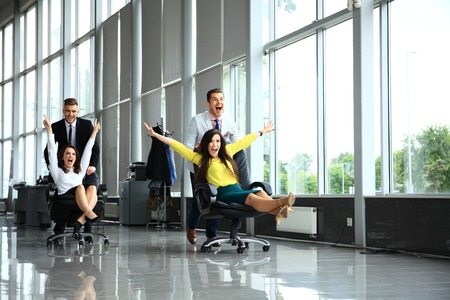 Photo pour Cheerful colleagues having fun in office chairs. - image libre de droit