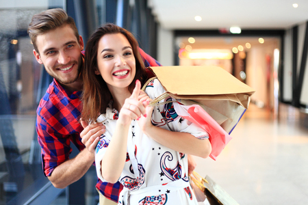 Foto de sale, consumerism and people concept - happy young couple with shopping bags walking in mall. - Imagen libre de derechos