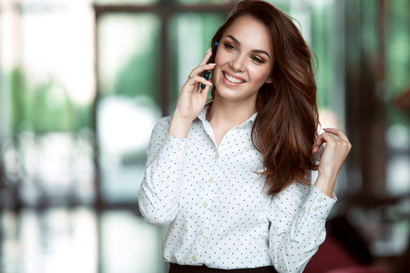Photo for Smiling businesswoman talking on the phone at the office. - Royalty Free Image