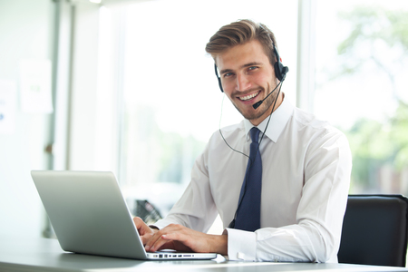 Foto de Happy young male customer support executive working in office. - Imagen libre de derechos