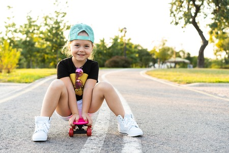 Photo for Fashion little girl child sitting on skateboard in city, wearing a sunglasses and t-shirt. - Royalty Free Image