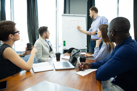 Foto de Discussing company progress. Confident young man standing near whiteboard and pointing graph while his colleagues sitting at the desk. - Imagen libre de derechos