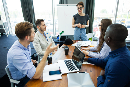 Foto de Discussing new business ideas. Cheerful young woman standing near whiteboard and smiling while her colleagues sitting at the desk. - Imagen libre de derechos