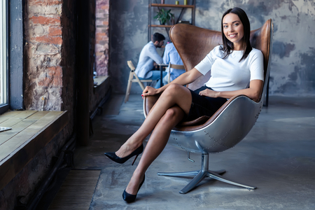 Foto de fashionable model sitting in a chair in office. Business, elegant businesswoman. - Imagen libre de derechos