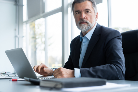 Photo pour Senior businessman working on laptop computer in the office. - image libre de droit
