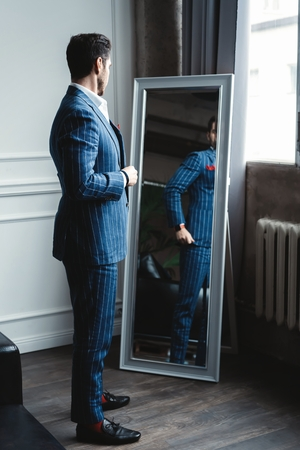 Photo for Perfect look. Reflection of handsome young man in full suit adjusting his jacket while standing in front of the mirror indoors. - Royalty Free Image