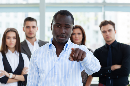Photo pour Handsome man pointing his finger at you on the background of business people. - image libre de droit