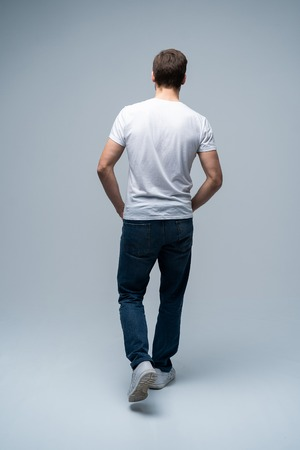 Foto de back view of a casual young man walking and looking to side on gray background. - Imagen libre de derechos