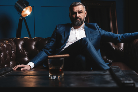 Foto per Attractive man with cigar and a glass whiskey - Immagine Royalty Free