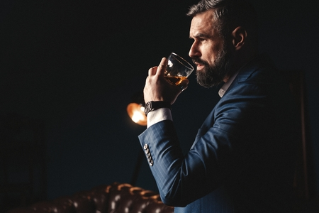 Photo pour Degustation, tasting. Man with beard holds glass of brandy. Tasting and degustation concept. Bearded businessman in elegant suit with glass of whiskey - image libre de droit