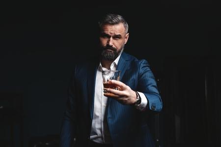 Foto de Attractive man with cigar and a glass whiskey - Imagen libre de derechos