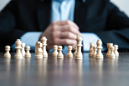 Foto de Businessman with clasped hands planning strategy with chess figures on table. Strategy, leadership and teamwork concept. - Imagen libre de derechos