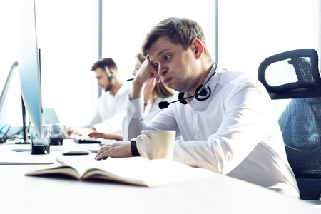 Photo pour Worried or tired business man with headset working on computer in office. - image libre de droit