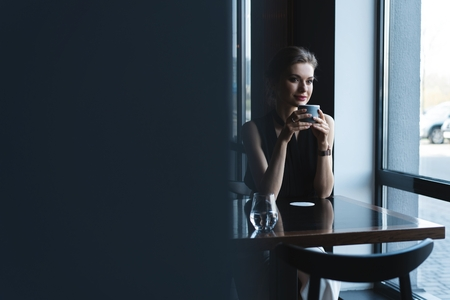 Foto de Portrait of gorgeous female drinking tea or coffee and looking with smile out of the coffee shop window while enjoying her leisure time - Imagen libre de derechos
