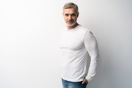 Foto de Cheerful man of middle age against white background, wearing jeans and white T-shirt, mid shot. - Imagen libre de derechos