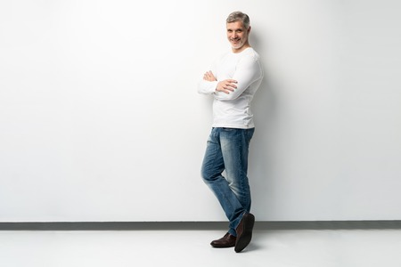 Foto de Full body portrait of relaxed mature man standing with arms crossed over white background. - Imagen libre de derechos