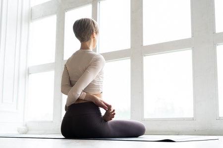 Photo pour Young attractive smiling woman practicing yoga, sitting in Half Lotus exercise, Ardha Padmasana pose, working out, wearing sportswear. - image libre de droit