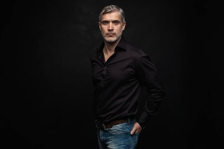Photo pour Middle-aged good looking man posing in front of a black background with copy space. - image libre de droit