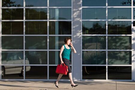 Yound Asian woman walks briskly while talking on the cell phone. She is carrying a red handbag. Horizontally framed photo.
