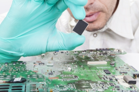 Photo pour Holding Microchip on electronic circuit board with Gloves - image libre de droit