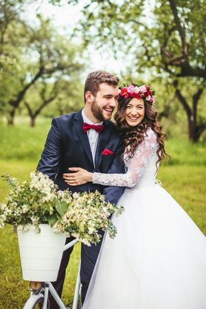 Photo pour Beautiful bride & groom posing near vintage provence bicycle outdoor - image libre de droit