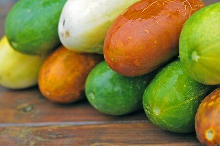 cucumbers; ripe; vibrant; zucchini; squash; green background; colorful; edible; food; vegetables; vitamins; a lot; autumn; harvest; balance; abundance; table; wooden, pile,
