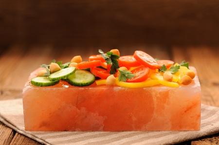 Photo for Vegetable salad on pink salt block on stripe napkin and wooden background - Royalty Free Image