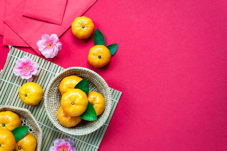 Foto de Top view  accessories Chinese new year festival decorations.orange,leaf,wood basket,red packet,plum blossom on red background. - Imagen libre de derechos