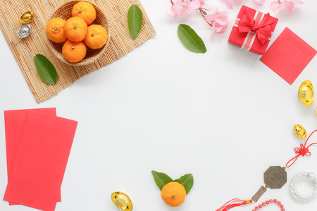 Foto de Top view shot of arrangement decoration Chinese new year & lunar festival concept background.Orange & tea pot also red pocket money with map to travel.Variety object on modern brown wood at home desk. - Imagen libre de derechos