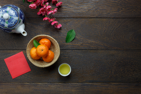 Photo pour Top view aerial image of accessory decoration Chinese new year & lunar holiday background concept.Flat lay Orange & flower also red pocket money.Variety object on modern brown wood at office desk. - image libre de droit