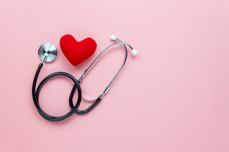 Foto de Table top view aerial image of accessories healthcare & medical background concept.Red heart & stethoscope with copyspace on pink paper.Flat lay of idea for doctor treat patient in hospital. - Imagen libre de derechos